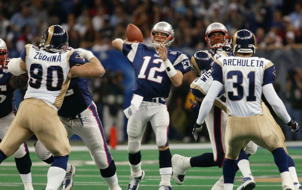 New England Patriots quarterback Tom Brady (12) throws as St. Louis Rams' Jeff Zgonina (90) and Adam Archuleta (31) defend during the third quarter of Super Bowl XXXVI at the Louisiana Superdome, Sunday, Feb. 3, 2002, in New Orleans. (AP Photo/Doug Mills)