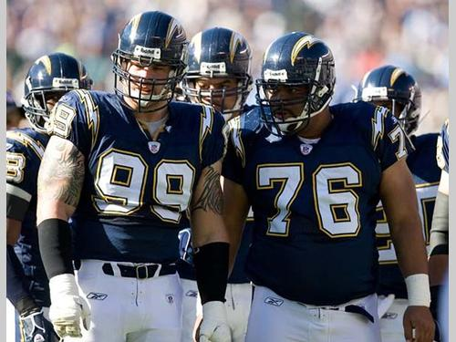 Defensive End Igor Olshansky (#99) and Defensive Tackle Jamal Williams (#76) look over to the Patriots' huddle during the AFC Divisional Playoff Game on Sunday, January 14, 2007 at Qualcomm Stadium in San Diego, CA.