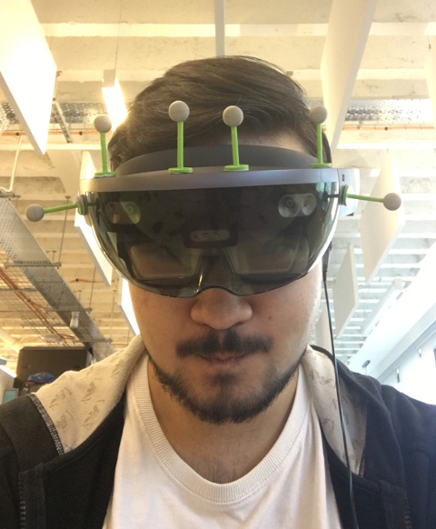 A picture of me wearing the HoloLens. There are some IR markers attached to it.