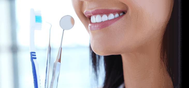 Lächelnde Frau mit Zahnbürste und Zahnarztinstrumenten.