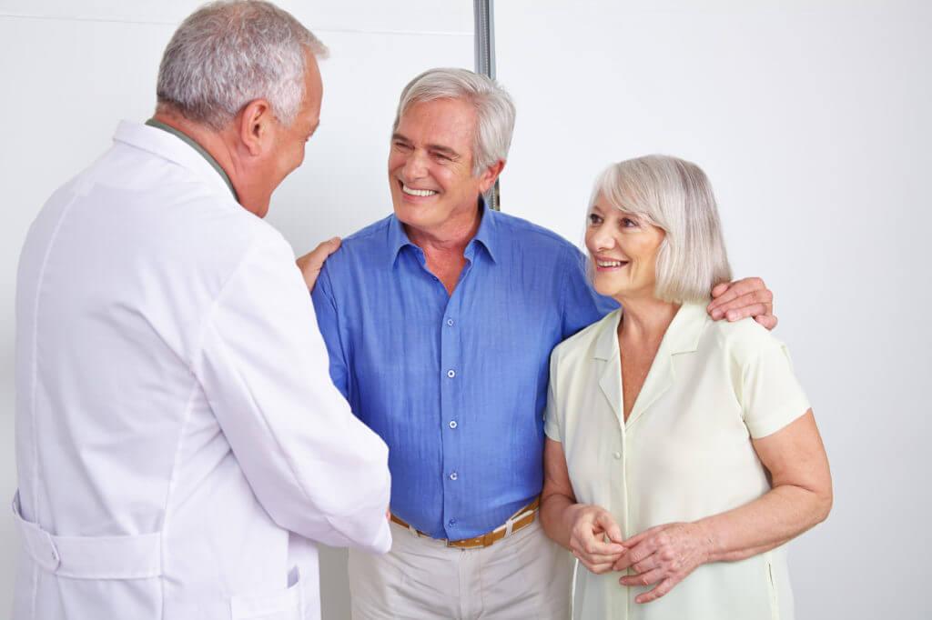 Arzt schüttelt lächelndem Paar die Hand.