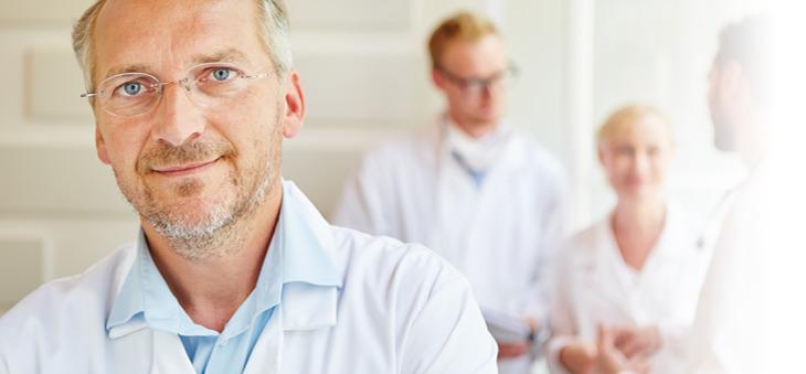 Arzt mit Brille im Vordergrund und drei weitere Ärzte im Hintergrund.