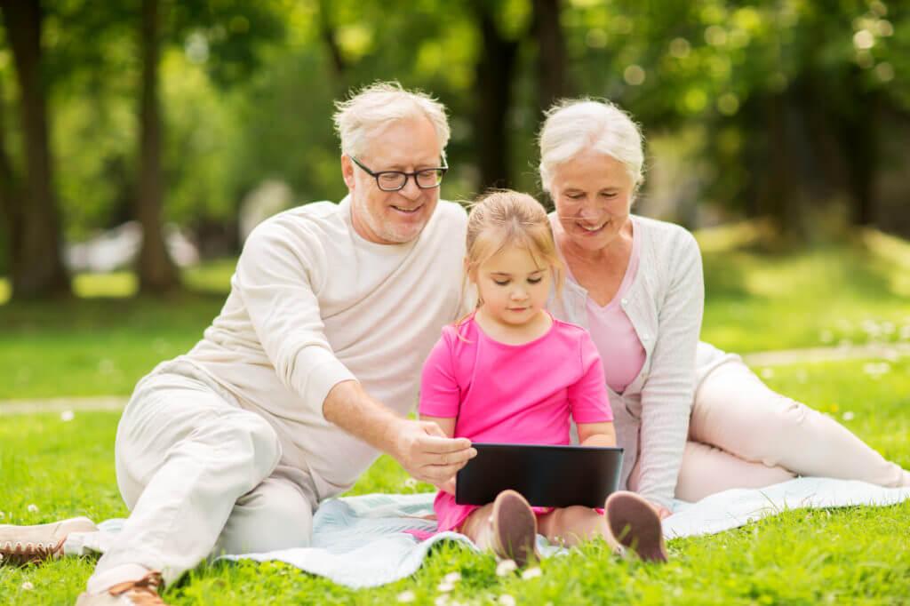 Frau und Mann sitzen mit Mädchen und Tablet-PC auf grüner Wiese.