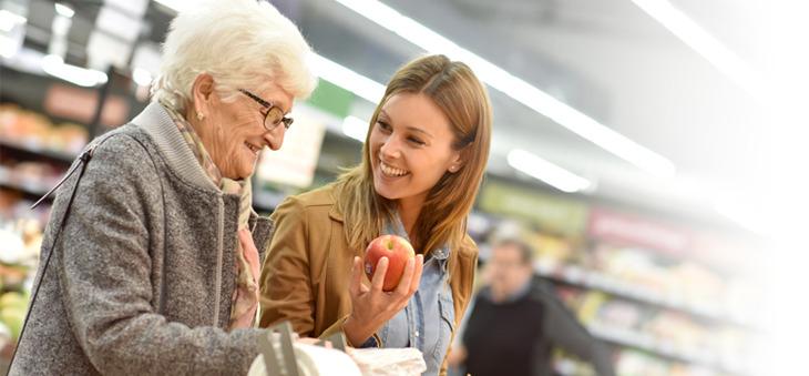 Seniorin und junge Frau kaufen Lebensmittel.