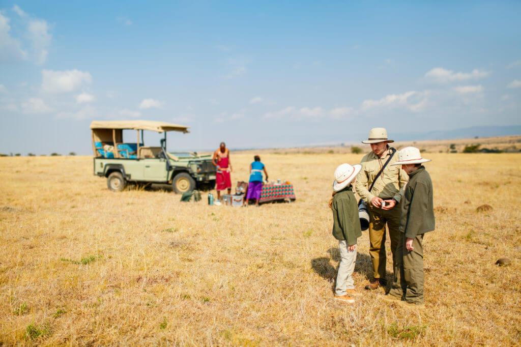 Touristen mit Safarihüten in der Savanne Afrikas, vor parkendem Fahrzeug.
