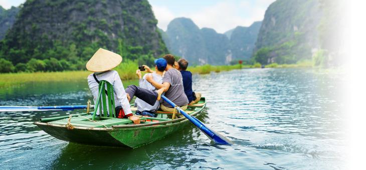 Kleines Boot mit Touristen und Bootsführer auf einem Fluss in Asien.