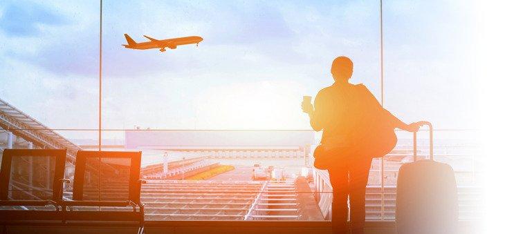 Reisende am Flughafen sieht startendem Flugzeug zu.