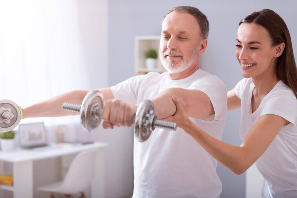 Therapeutin hilft Patient bei einer Hantelübung.