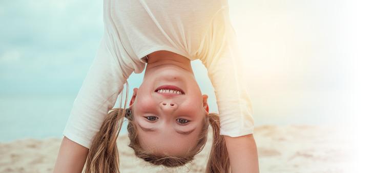 Kleines Mädchen lächelt beim Handstand am Strand.