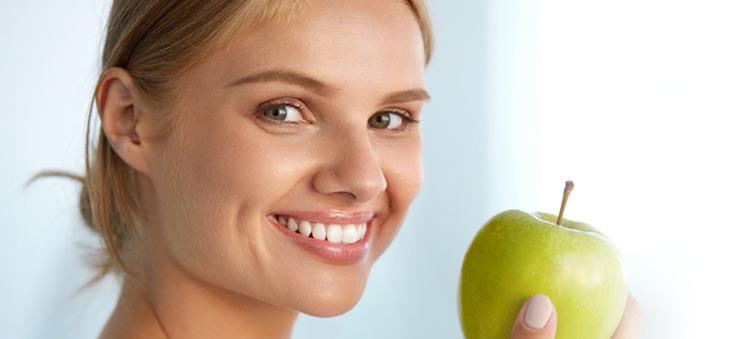 Lächelnde junge Frau mit grünem Apfel in der Hand.
