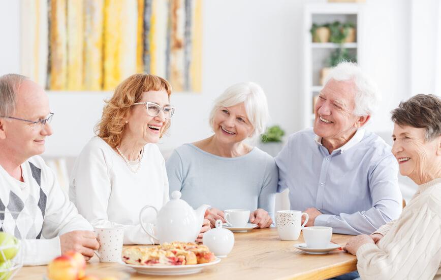 Senioren-Gruppe sitzt lächelnd bei Kaffee und Kuchen am Tisch.