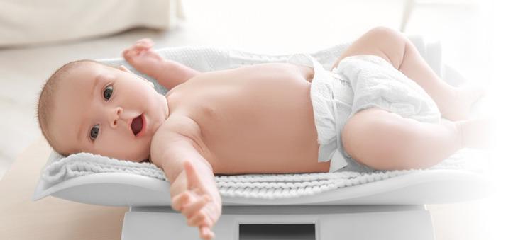 Baby mit Windel liegt auf einer Waage.