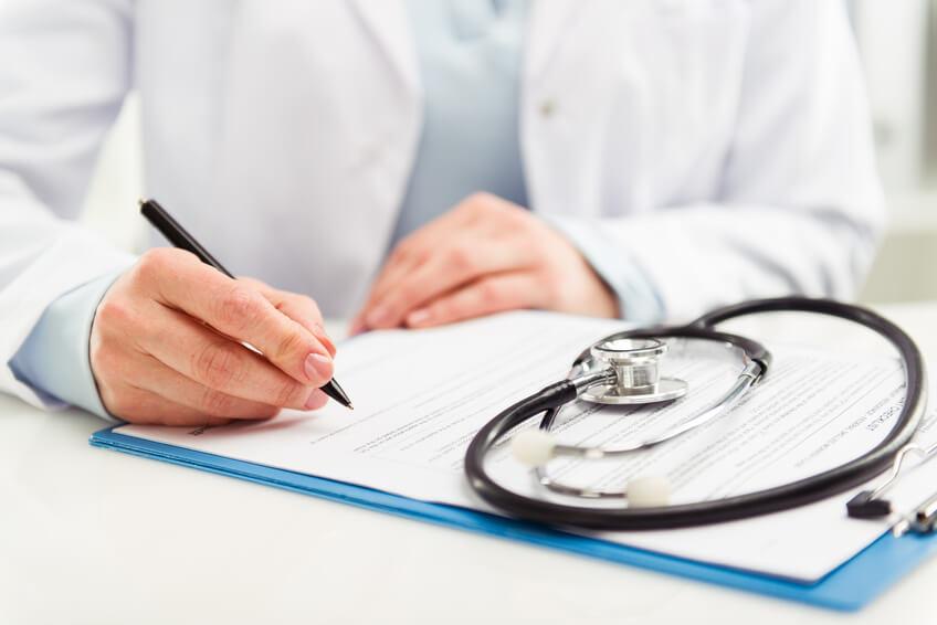 Arzt füllt Dokument aus.