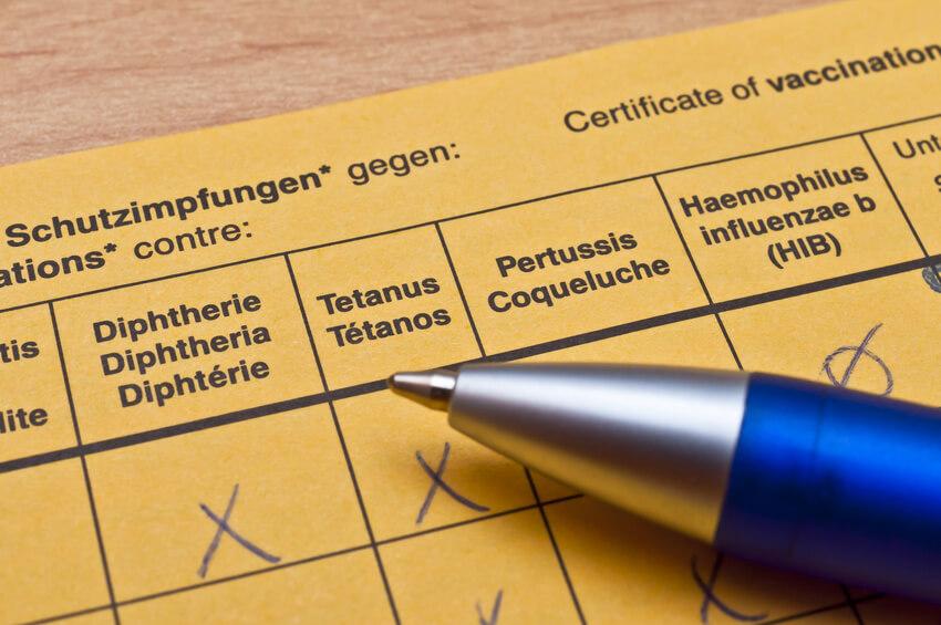 Impfausweis und Kugelschreiber.