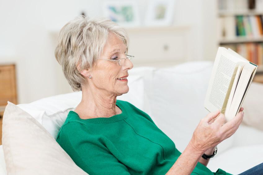 Ältere Frau mit Brille ließt auf dem Sofa.