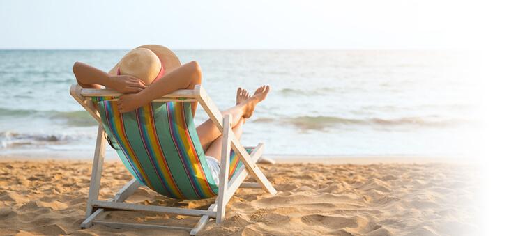 Urlauberin mit Strohhot im Liegestuhl am Meer.