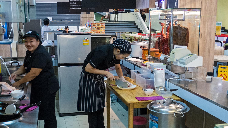 Frauen bereiten Essen in einer asiatischen Restaurantküche zu.