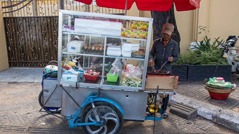 Mann kocht am Streetfood-Stand.