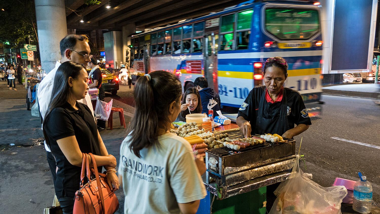 Streetfood-Stand in Asien mit Gästen.