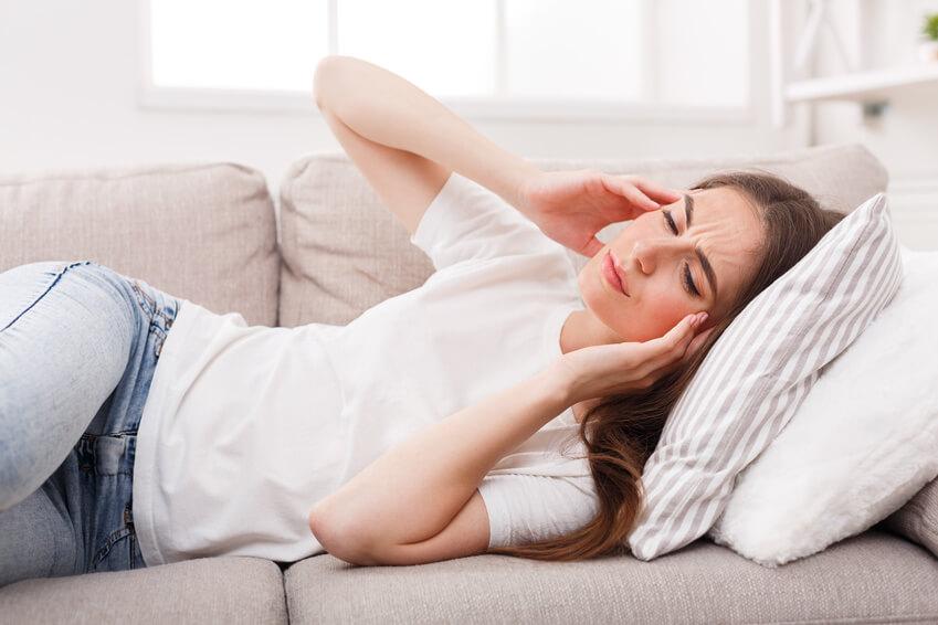 Junge Frau liegt auf dem Sofa und hält sich die Schläfen.