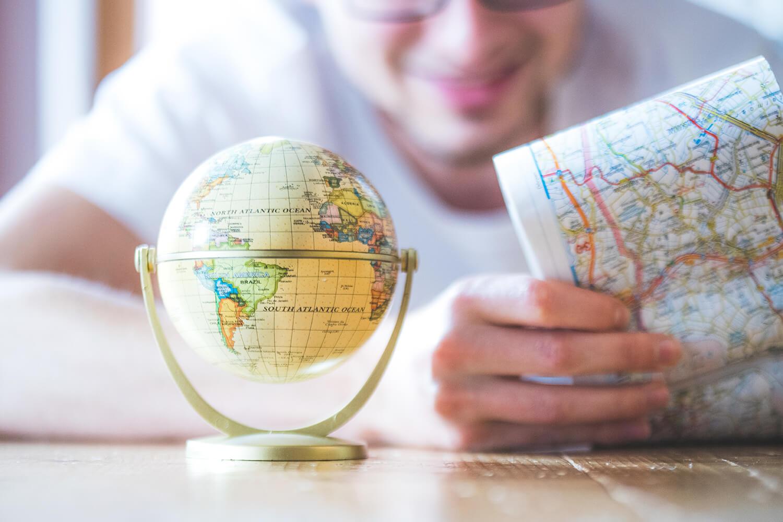 Mann liest Landkarte vor einem Globus.