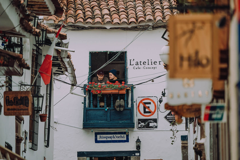 Zwei Männer sitzen auf kleinem Balkon.