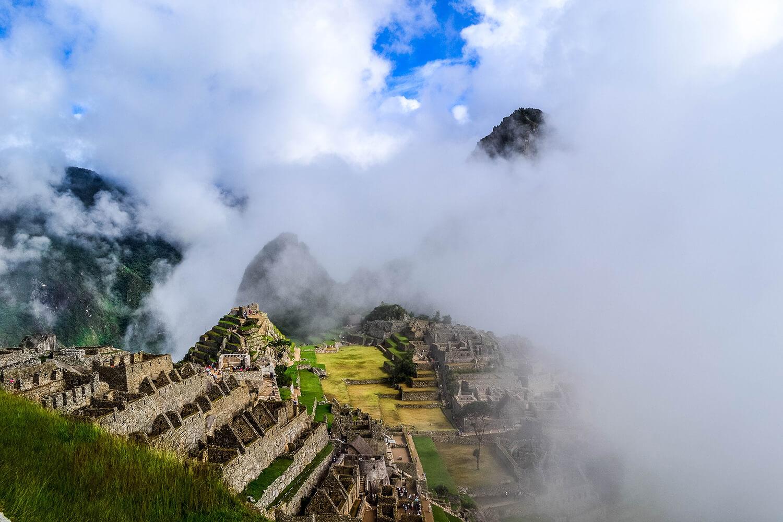 Machu Pichu in den Wolken zwischen Berggipfeln.