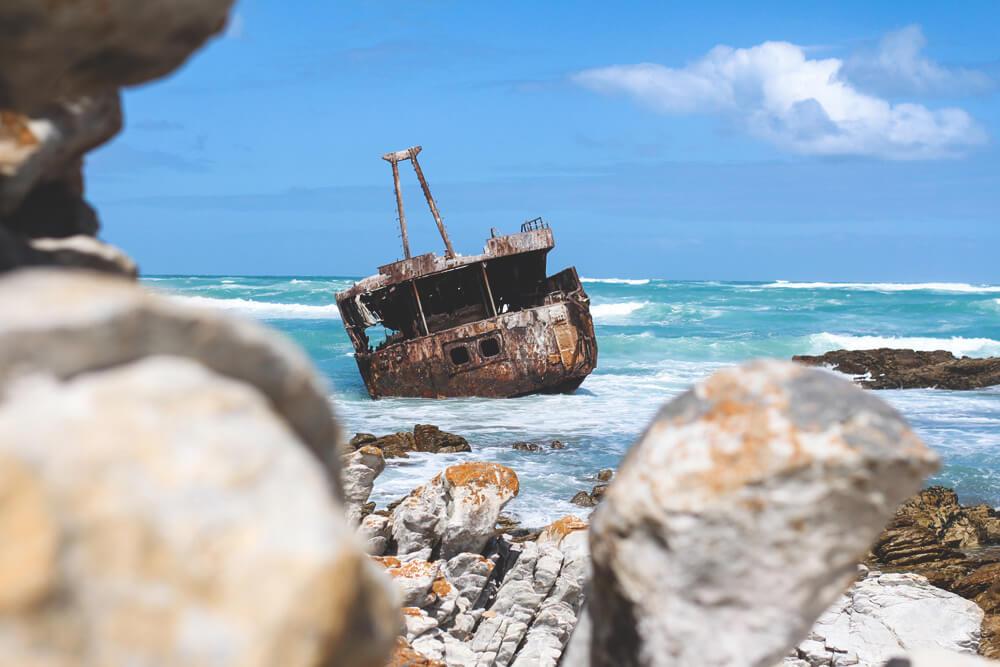 Schiffswrack mit Schlagseite liegt am Cape Aghulas an einem Steinstrand im Meer.