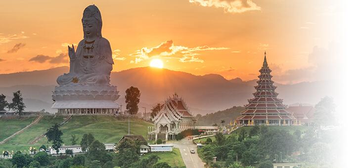 Riesige Buddhastatue und Tempel vor Hügellandschaft in Südostasien.