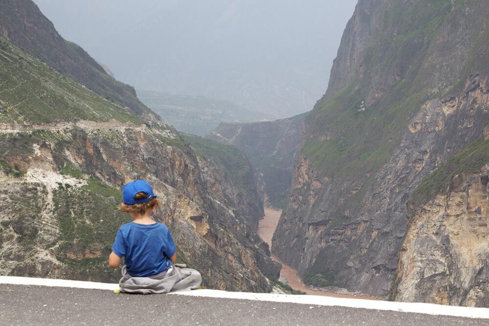 Kind sitzt auf Betonbrüstung vor Bergkulisse.