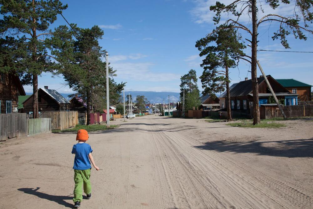 Junge geht sandige Straße entlang.