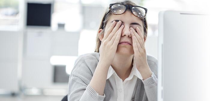 Junge Frau sitzt am PC und reibt sich die Augen.