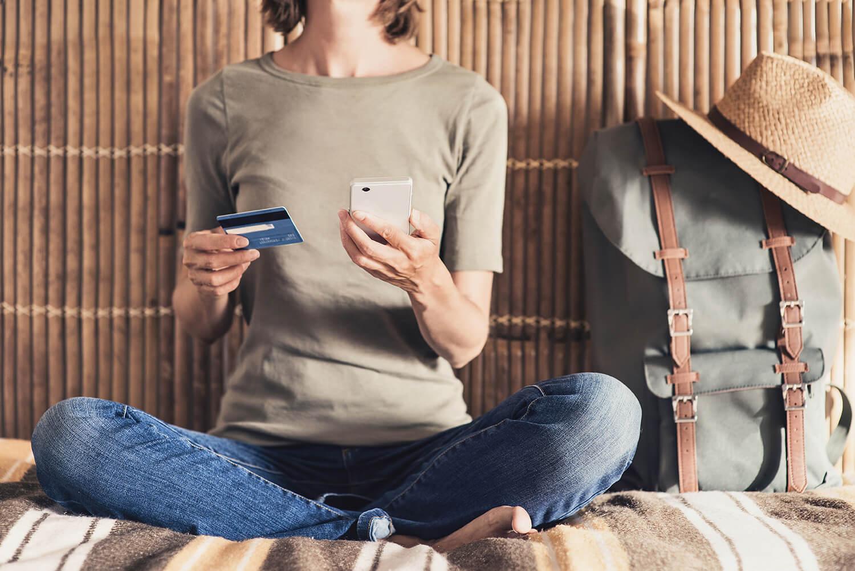 Junge Frau mit Smartphone sitzt neben großem Rucksack vor einer Bambuswand.
