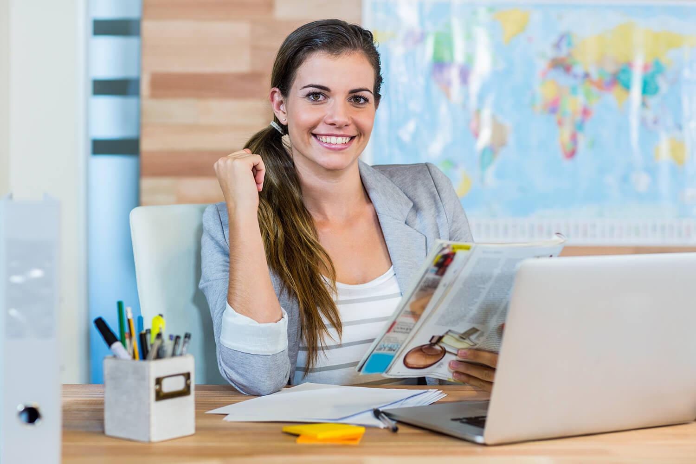 Junge Frau mit Laptop vor Weltkarte.