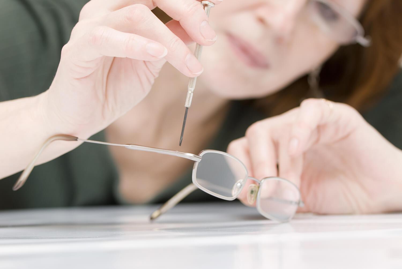 Frau setzt Schraubenzieher an Brille an.
