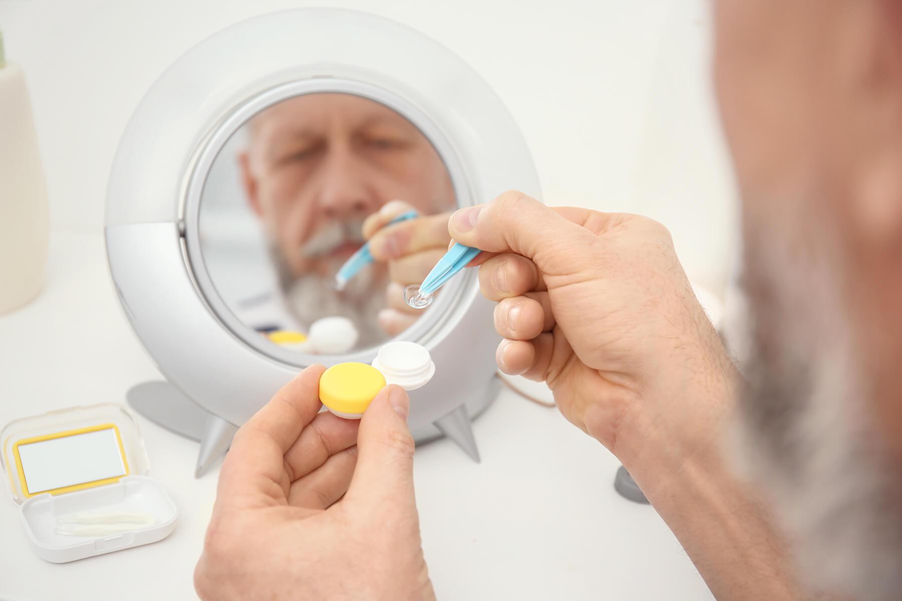 Mann vor Spiegel bewegt Kontaktlinse mit Pinzette.