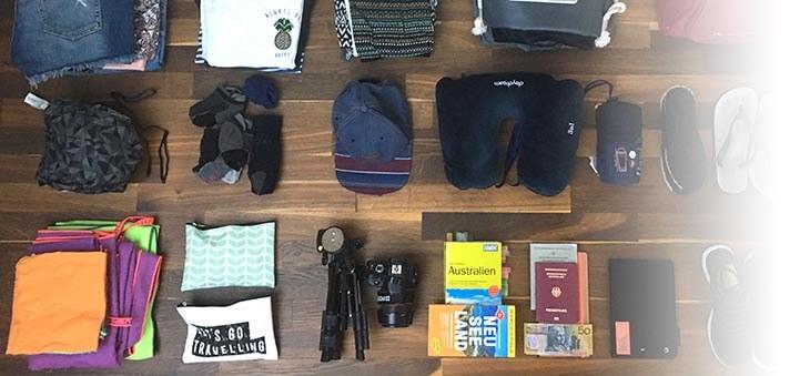Gestapelte Kleidung, Equipment und Reiseunterlagen.