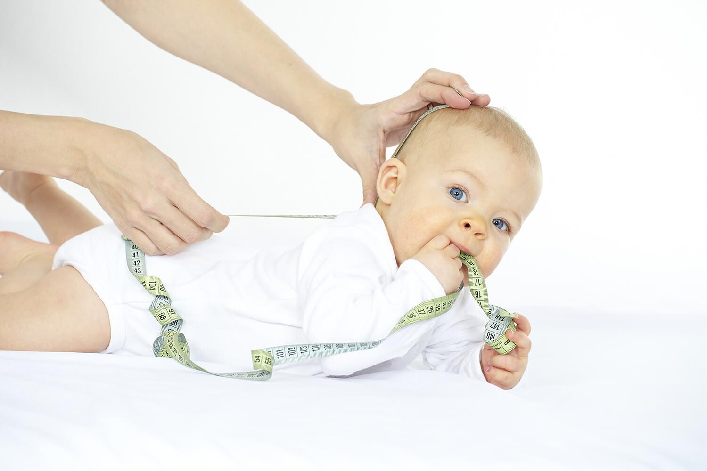 Hände legen Maßband an Baby an, während Baby das Band in den Mund nimmt.