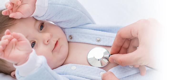 Baby hebt die Hände und wird an der Brust mit Stetoskop abgehört.