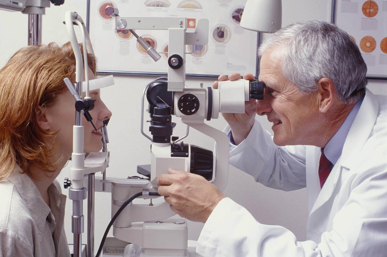 Augenarzt untersucht die Augen einer Patientin.