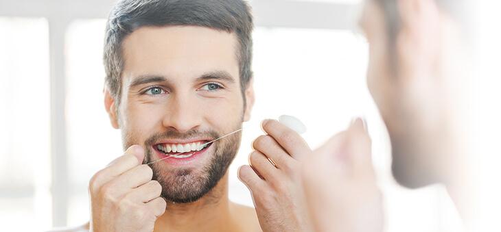 Mann benutzt Zanhseide vor dem Spiegel.