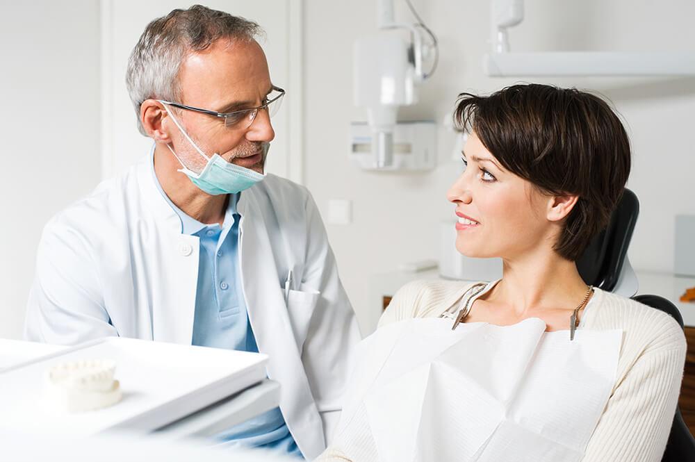 Zahnarzt spricht mit Patientin.