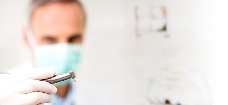 Zahnarzt hält Bohrer.
