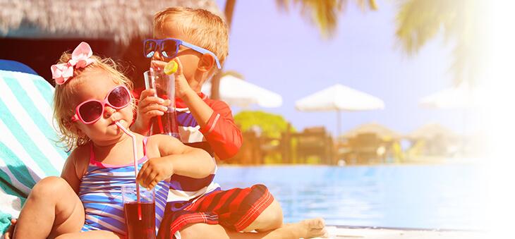 Zwei Kleinkinder sitzen mit Sonnenbrillen und Drinks am Pool.