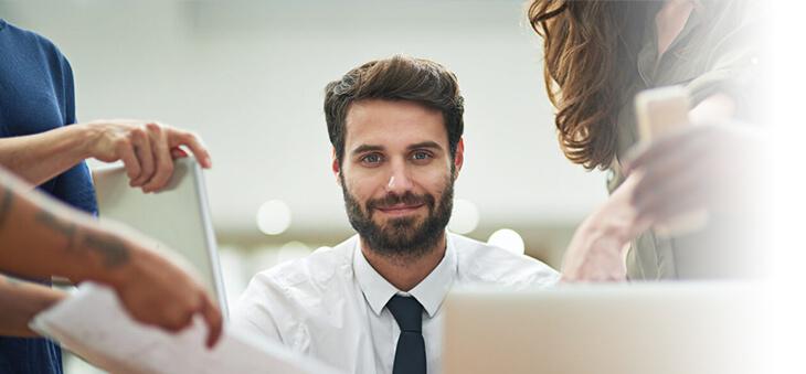 Lächelnder Mann zwischen Personen mit Laptops, Dokumenten und Smartphones.