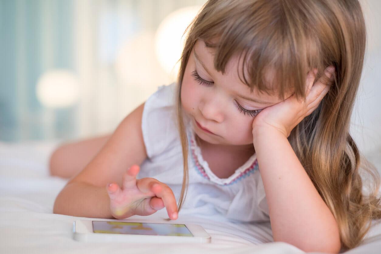 Kleines Mädchen tippt auf Smartphone-Display.