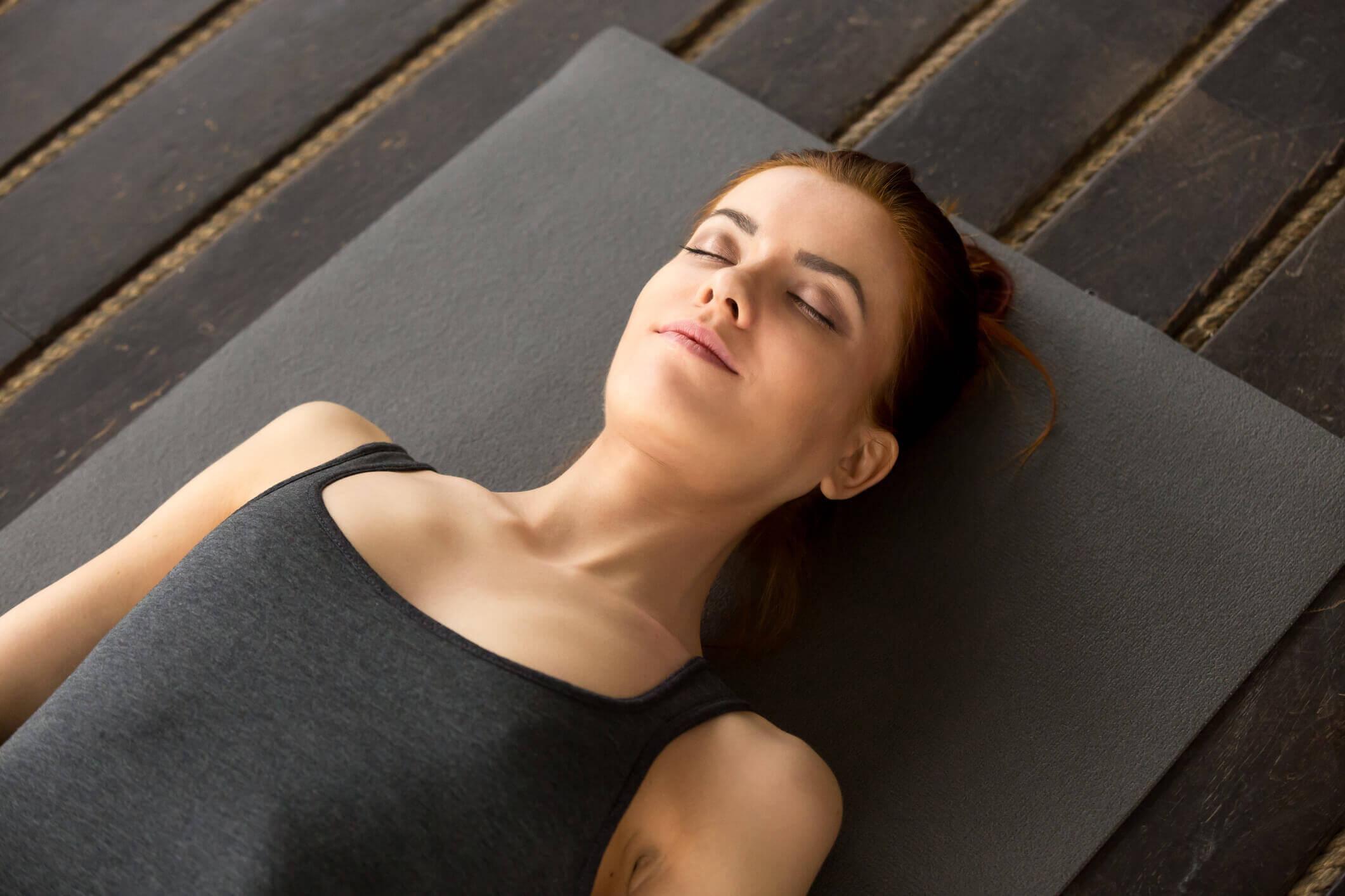 Frau liegt entspannt auf einer Yogamatte.