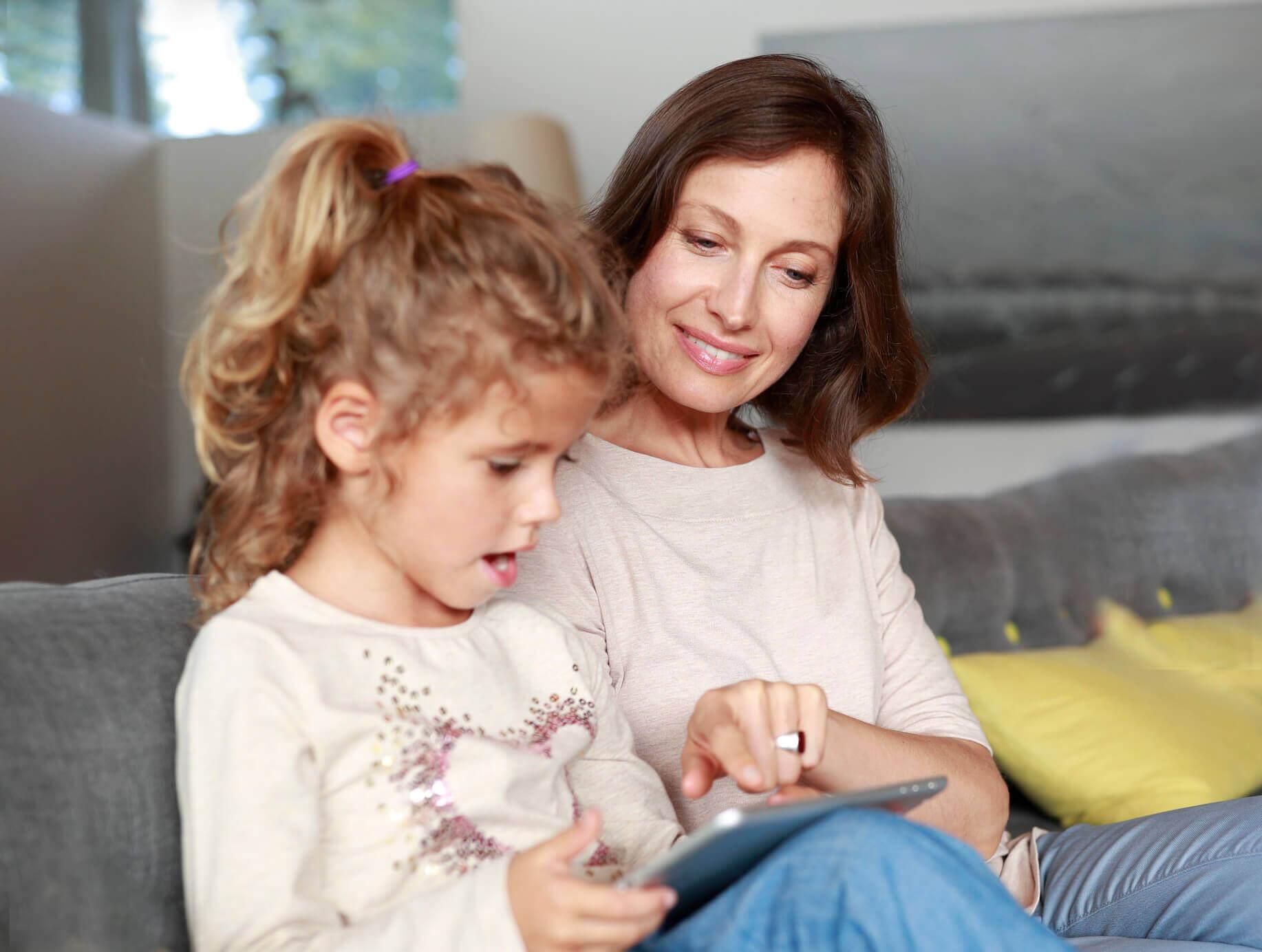 Frau und Kind sitzen mit Tablet-PC auf dem Sofa.