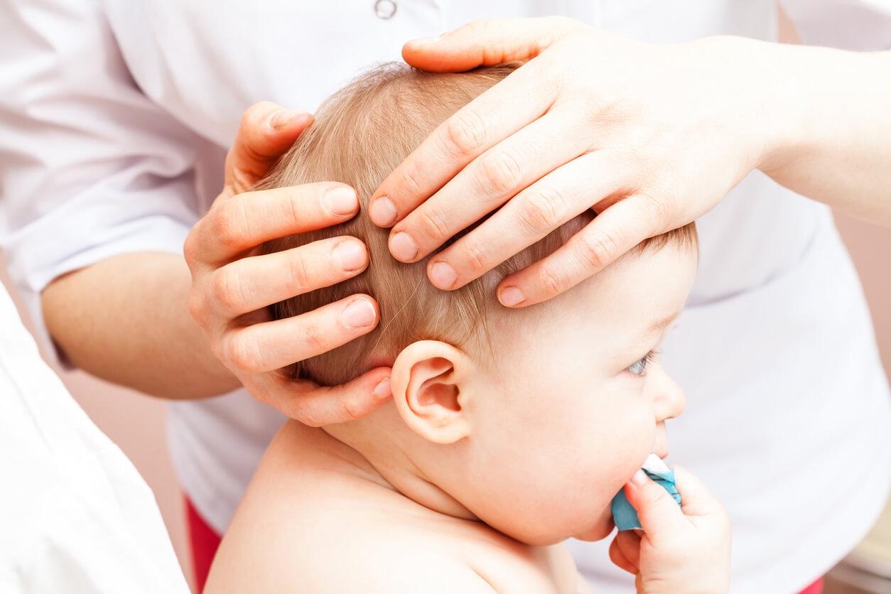 Therapeut hält Babyköpfchen in den Händen.