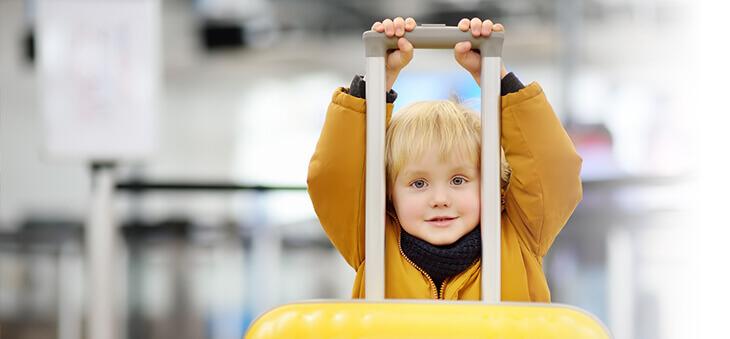 Kleines Kind hält großen Koffer.